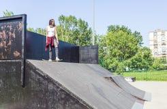 Skateboardermeisje die bij de helling van het vleetpark met een skateboard rijden stock afbeelding