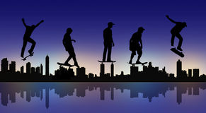 Skateboarders with a night city silhouette Royalty Free Stock Photos