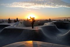 Skateboarders in park at sunset