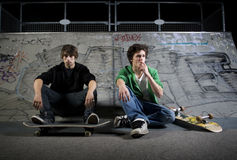 Skateboarders sitting in skatepark Stock Images