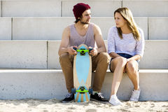 Skateboarders Sitting On Steps At Beach Stock Photo