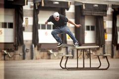 Skateboardfahrer, der ein gekrümmtes Schleifen auf einem Picknicktisch tut Stockbilder