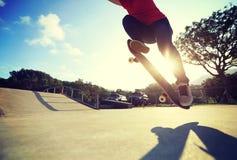 Skateboardfahrer, der ein Trick ollie am skatepark tut stockbilder