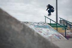 Skateboardfahrer, der einen Ollie über der Schiene in einem skatepark tut Lizenzfreie Stockbilder
