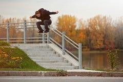 Skateboardfahrer, der einen Ollie hinunter die Treppe tut Stockfotografie