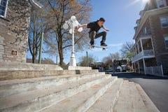 Skateboardfahrer, der einen Ollie hinunter die Treppe tut Stockbild