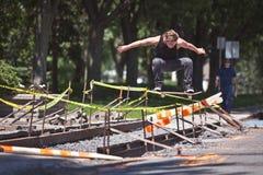 Skateboardfahrer, der einen Ollie-Trick über Bau tut Lizenzfreies Stockfoto