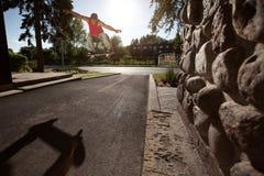 Skateboardfahrer, der einen Ollie-Trick in der Straße tut Stockfotografie
