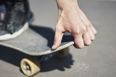 Skateboardfahrer, der einen Trick in einem Rochenpark, altes Skateboard der Nahaufnahme tut stockfoto