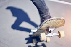 Skateboardfahrer, der einen Trick in einem Rochenpark, altes Skateboard der Nahaufnahme tut lizenzfreies stockfoto