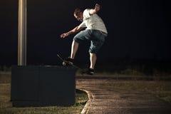Skateboardfahrer, der einen Trick Frontside Boardslide nachts tut stockbild