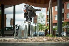 Skateboardfahrer, der Ollie Over ein Fahrrad-Gestell tut Lizenzfreie Stockfotos