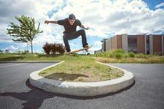 Skateboardfahrer, der Ollie Over ein Gras-Abschnitt tut Stockbilder