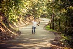 Skateboardfahrer, der seine Hände oben auf der Straße im Wald anhebt Stockfoto