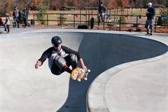 Skateboardfahrer ergreift das Brett, das Trick in der großen Schüssel tut Stockfotos