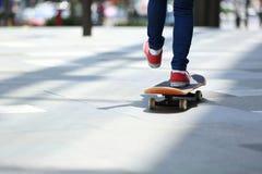Skateboardfahrerbeine, die auf Skateboard auf Stadt fahren Lizenzfreies Stockbild
