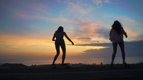 Skateboarding силуэт 2 девушек против неба и солнца акции видеоматериалы