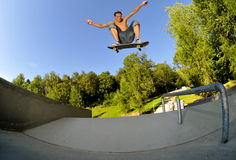 Skateboarding. Young adult having fun while skateboarding at the skatepark Stock Photos