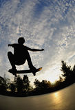 Skateboarding. Silhouette of a young adult having fun while skateboarding at the skatepark Royalty Free Stock Photo