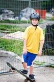 Skateboarding boy. Boy outdoors skateboarding wearing a helmet Royalty Free Stock Photos