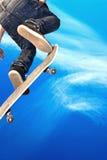 Skateboarding boy. Boy with skateboard going airborne royalty free stock image