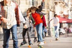 Skateboarding de l'adolescence heureux avec des amis à la promenade latérale Photos libres de droits