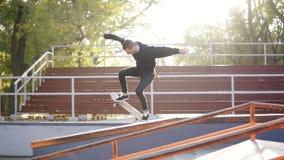 Skateboarding del skater y truco de salto del tirón sobre el tubo y el caer abajo en la calle concreta skateboarder metrajes
