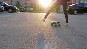 Skateboarding della ragazza sulla via della città sul fondo di luce solare e sull'architettura urbana Pattino di guida della raga archivi video