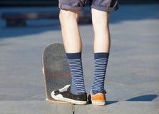 Skateboarding - detail of skateboard and legs. Stock Photography