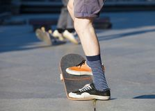 Skateboarding - detail of skateboard and legs. Royalty Free Stock Photos