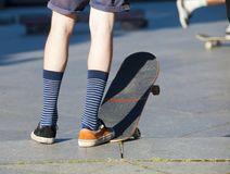 Skateboarding - detail of skateboard and legs. Royalty Free Stock Images