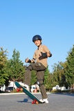 Skateboarding Fun. Smiling teenage boy with his thumbs up standing on a skateboard on a sunny day with blue sky and trees in the background Stock Images