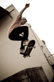 Skateboarding Jump. A young skateboarder launches off a concrete loading dock in an urban setting stock photos