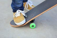 Skateboarding legs riding on a skateboard Royalty Free Stock Photos