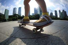 Skateboarding på soluppgångstaden arkivfoto