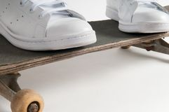 Skateboarding person stands with feet apart on a skateboard. Skateboarding person stands with feet apart on an old skateboard Royalty Free Stock Photo