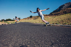 Skateboarding on the rural road. Young men and women skateboarding on the rural road. Young couple enjoying skating on the road Royalty Free Stock Image