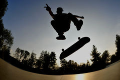 Skateboarding silhouette. Skateboarder flying high at the skate park in summertime Royalty Free Stock Photo