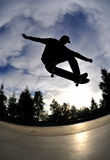 Skateboarding silhouette. Silhouette of a skateboarder performing a stylisch trick at the skatepark Stock Photos