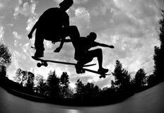 Skateboarding silhouettes. Skateboarders flying high at the skate park in summertime Stock Photo