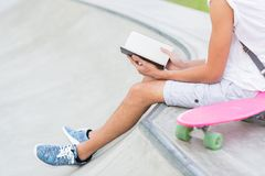 Closeup of young man reading at the skateboard park. stock image