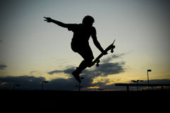 Skateboarding at sunset. A skateboarder skates in a skate park Royalty Free Stock Photos