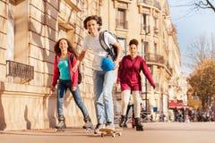 Skateboarding y muchachas del muchacho rollerblading en la ciudad Imagen de archivo