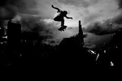Skateboardryttare i ett trick arkivfoton