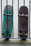 Skateboards. A pair of skateboards leaning against a fence in a park Royalty Free Stock Image
