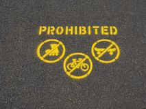 Skateboards, Bikes and Roller Skates Prohibited Sign. A freshly painted sign on an ashfelt walking path indicating that roller skates, bicycles and skateboards royalty free stock photo