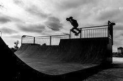 Skateboradåkare som gör trick i rampaen Arkivbild