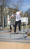 Skateboradåkare som maler en stång i en skridsko, parkerar Royaltyfri Fotografi