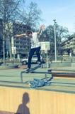 Skateboradåkare som maler en stång i en skridsko, parkerar Royaltyfri Bild