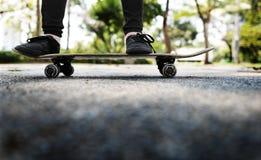 Skateboradåkare som skateboarding i parkera Royaltyfri Bild